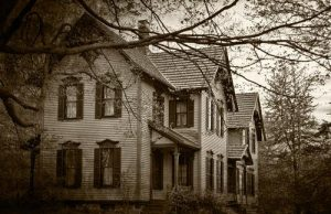 Black and white image of an old house, through tree branches.