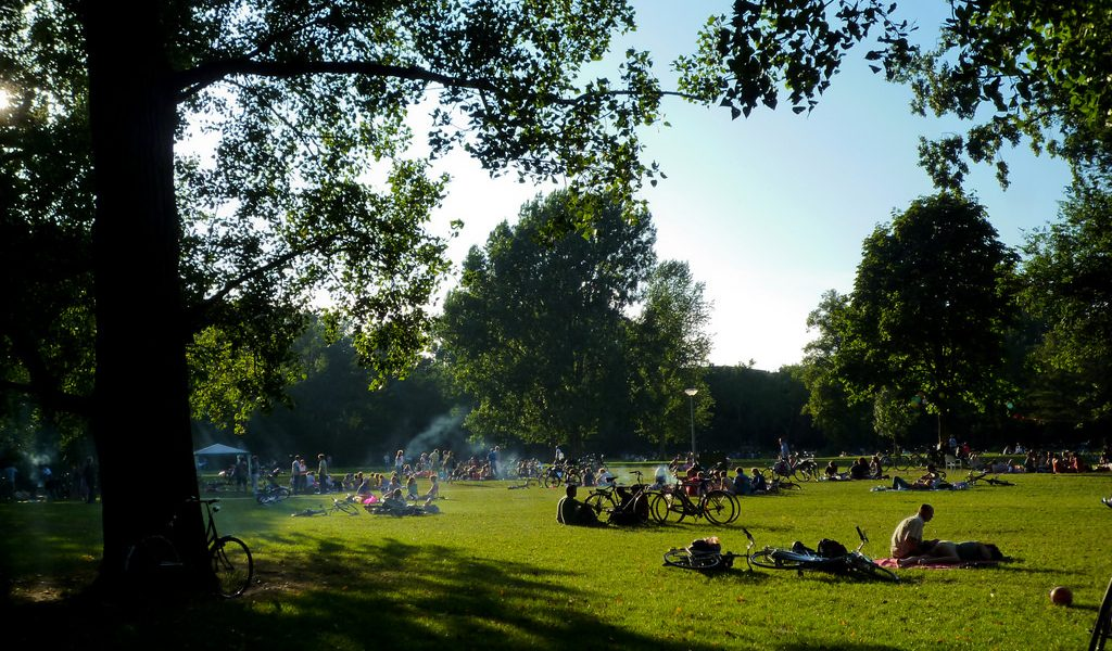 Lush city park in the summer time. People lounging in grass, crossing on bikes, bbqing.